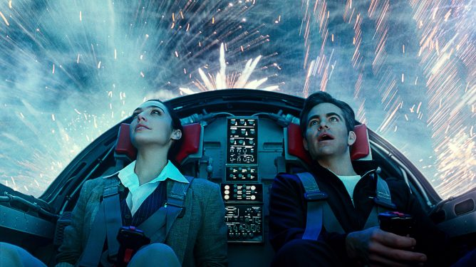 Gal Gadot and Chris Pine sit in the cockpit of a jet fighter as colorful fireworks blast around them from the outside as seen in Wonder Woman 1984.