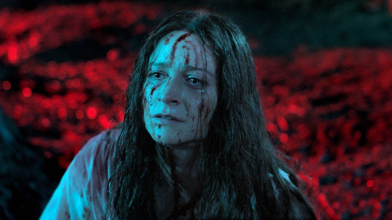 Niamh Algar in a bloody, dirty white gown as seen in Sundance 2021 horror film Censor.
