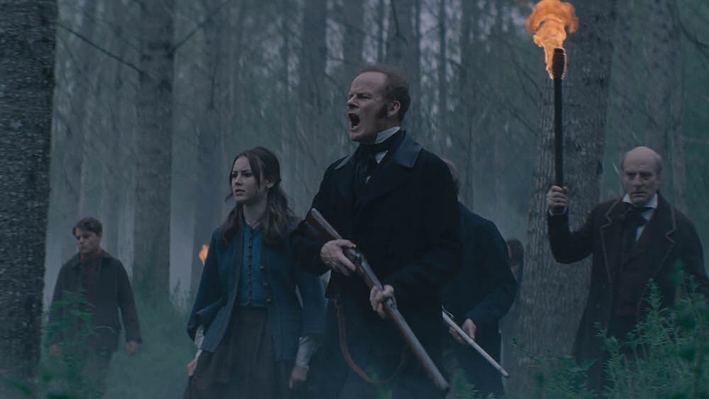 Alistair Petrie, Amelia Crouch, and Simon Kunz lead a search party in a gothic forest as seen in Eight for Silver directed by Sean Ellis.
