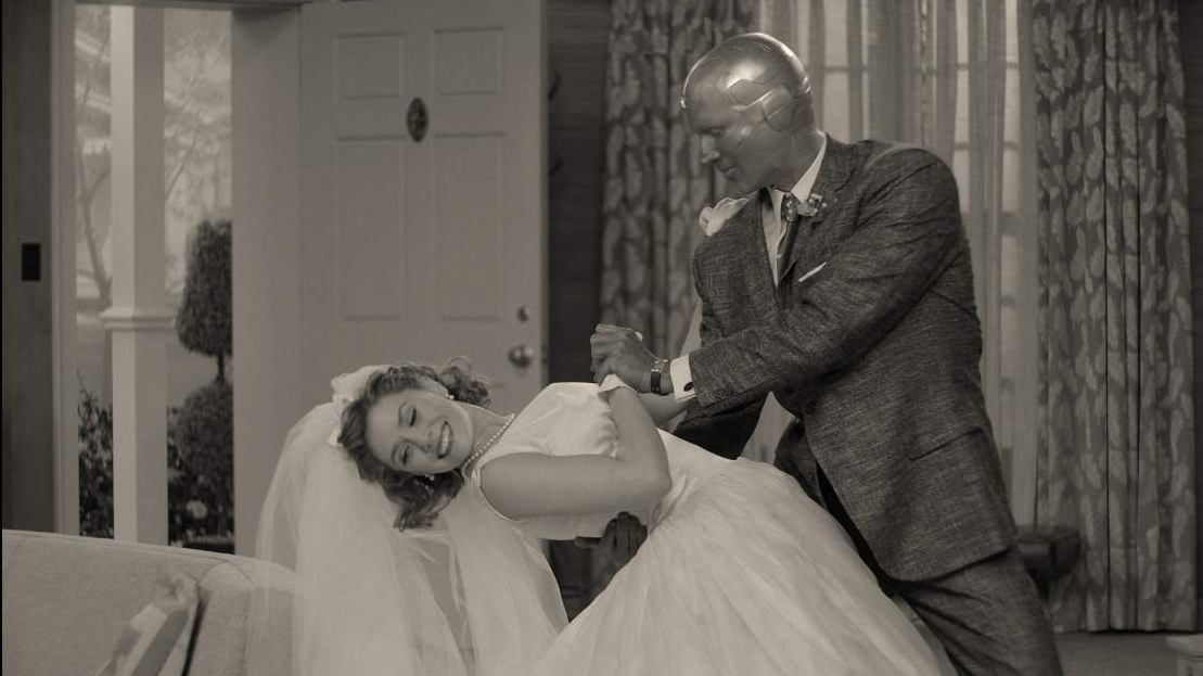 The Vision and Wanda Maximoff in their just married wedding clothes dance in their new living room in black-and-white as seen in WandaVision.