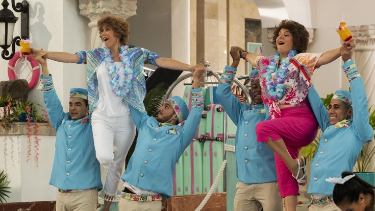 Kristen Wiig and Annie Mumolo are lifted by hotel staff during a musical number inside a colorful resort as seen in Barb and Star Go to Vista Del Mar directed by Josh Greenbaum.