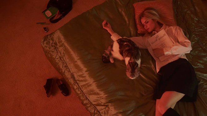 Carlson Young laying on a bed with a cat holding the script to her short film The Blazing World.