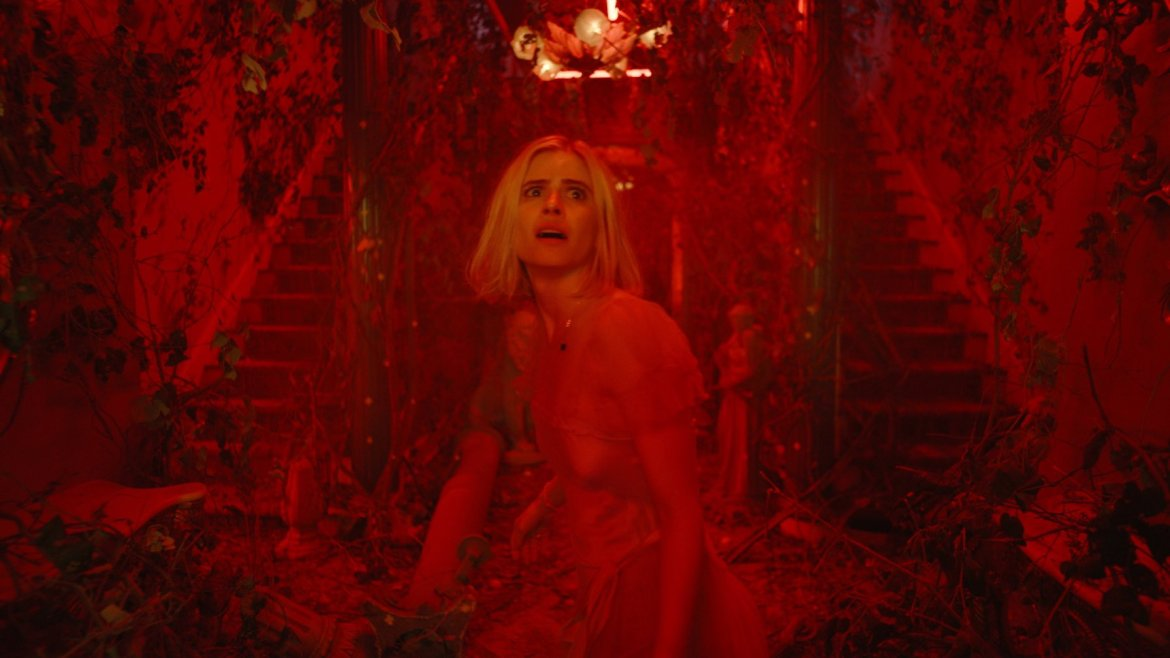 Carlson Young looking afraid in a blood red mansion as seen in her film The Blazing World.