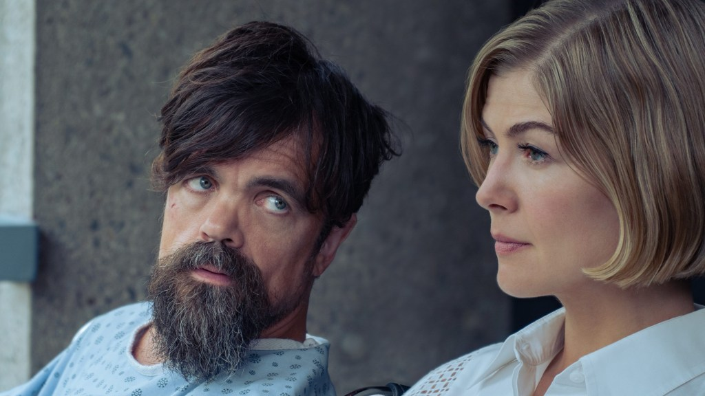 Peter Dinklage and Rosamund Pike sitting together as seen in the Netflix film I Care A Lot.