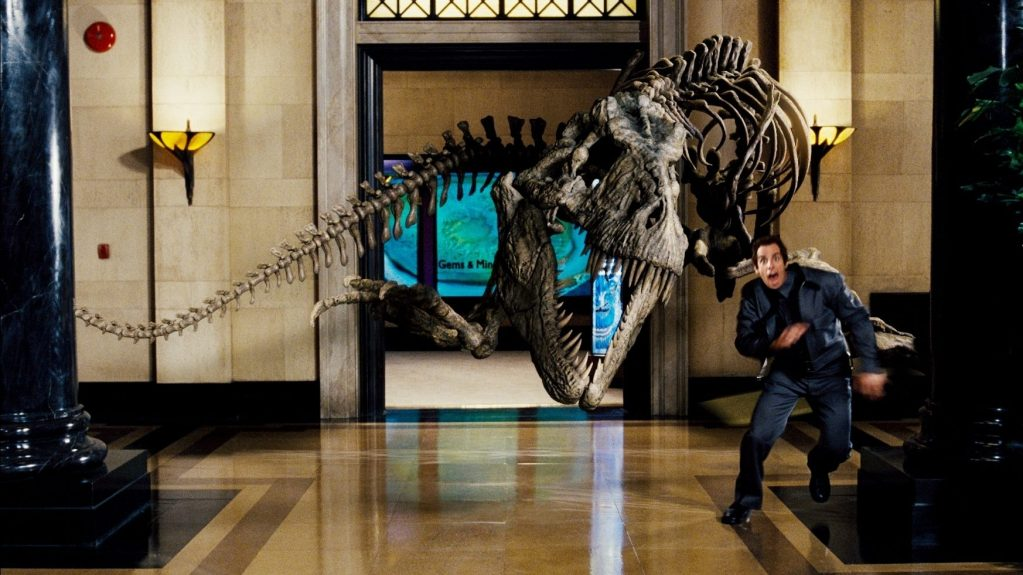 Ben Stiller as Larry Daley running away from Rexy the Tyrannosaur fossil skeleton in Night at the Museum.