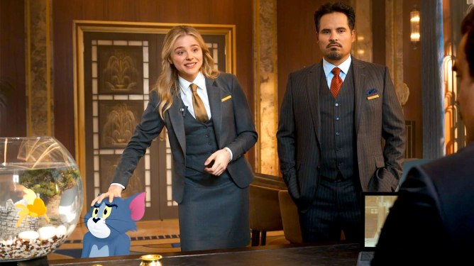 Chloë Grace Moretz and Michael Peña in a hotel's manager office with an animated Tom as seen in the 2021 film Tom & Jerry.