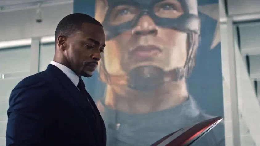 Anthony Mackie as Sam Wilson holding Captain America's shield in front of a monument as seen in The Falcon and the Winter Soldier.