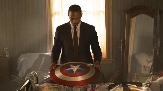 Anthony Mackie as Sam Wilson holding Captain America's shield in a suit and tie as seen in The Falcon and the Winter Soldier.
