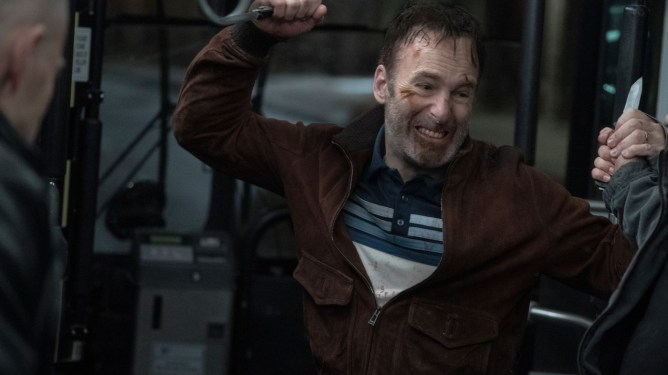 Bob Odenkirk in a bloody knife fight on a bus as seen in the action comedy Nobody.
