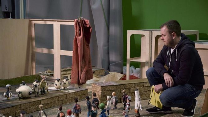 Director Richard Phelan on the set of A Shaun the Sheep Movie: Farmageddon  with all the miniature stop motion puppets.