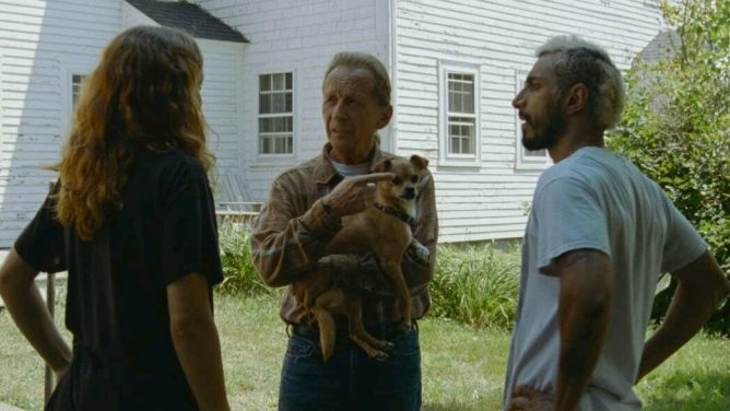 Olivia Cooke, Paul Raci holding a small dog, and Riz Ahmed standing together as seen in the 6 time Oscar-nominated film Sound of Metal.