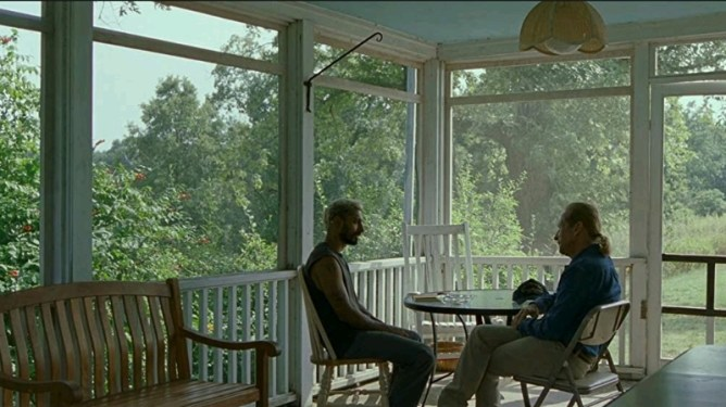 Riz Ahmed and Paul Raci sitting in a deaf sober house by a gorgeous field as seen in the Oscar nominated film Sound of Metal.