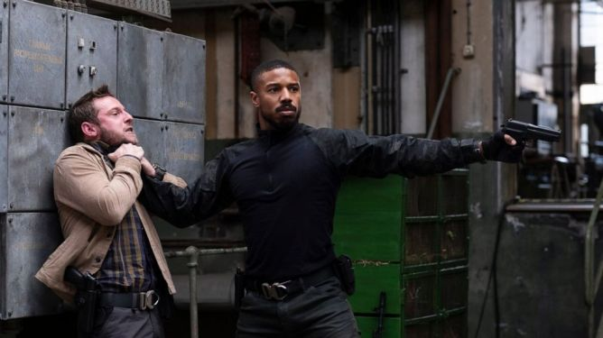 Michael B. Jordan holding Jamie Bell by the neck as he holds him for mercy with a gun as seen in the new Tom Clancy thriller Without Remorse.