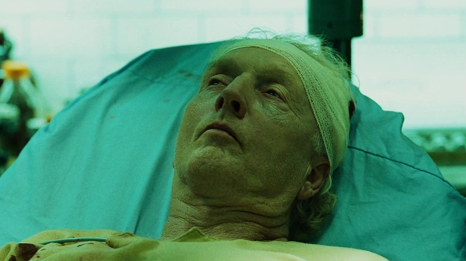 John Kramer played by Tobin Bell on his death bed as seen in the pivotal finale of Saw III.