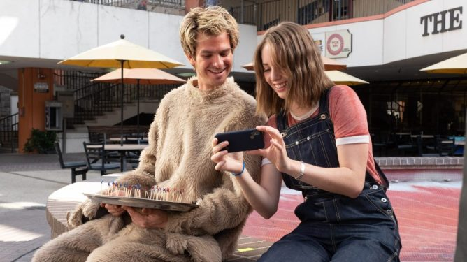 Andrew Garfield wearing a fuzzy suit with Maya Hawke as seen in Mainstream directed by Gia Coppola.