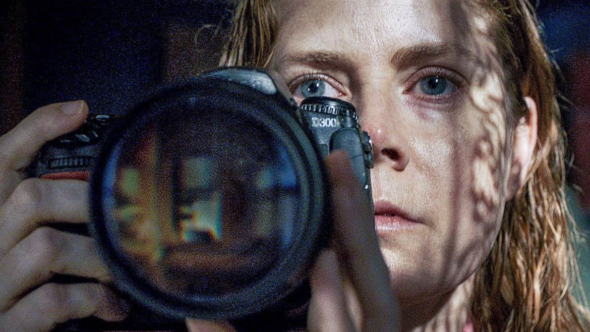 Amy Adams spying on her neighbors with a camera as seen in the new Netflix film The Woman in the Window.