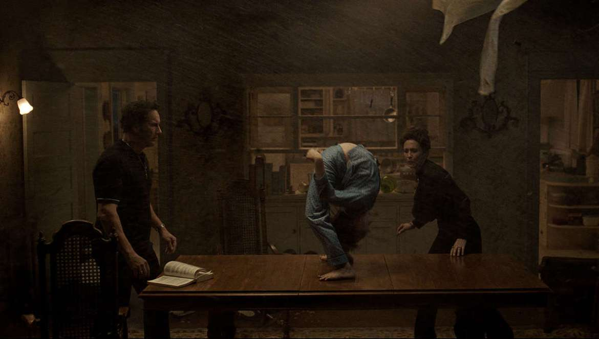 Patrick Wilson as Ed Warren and Vera Farmiga as Lorraine Warren performing an exorcism on a young boy as he bends over backwards on a table as seen in The Conjuring: The Devil Made Me Do It