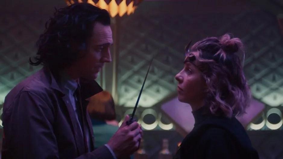 Tom Hiddleston as Loki holds a dagger to Sophia Di Martino as Lady Loki aka Sylvie on a fancy train as seen in Episode 3 of LOKI on Disney+.