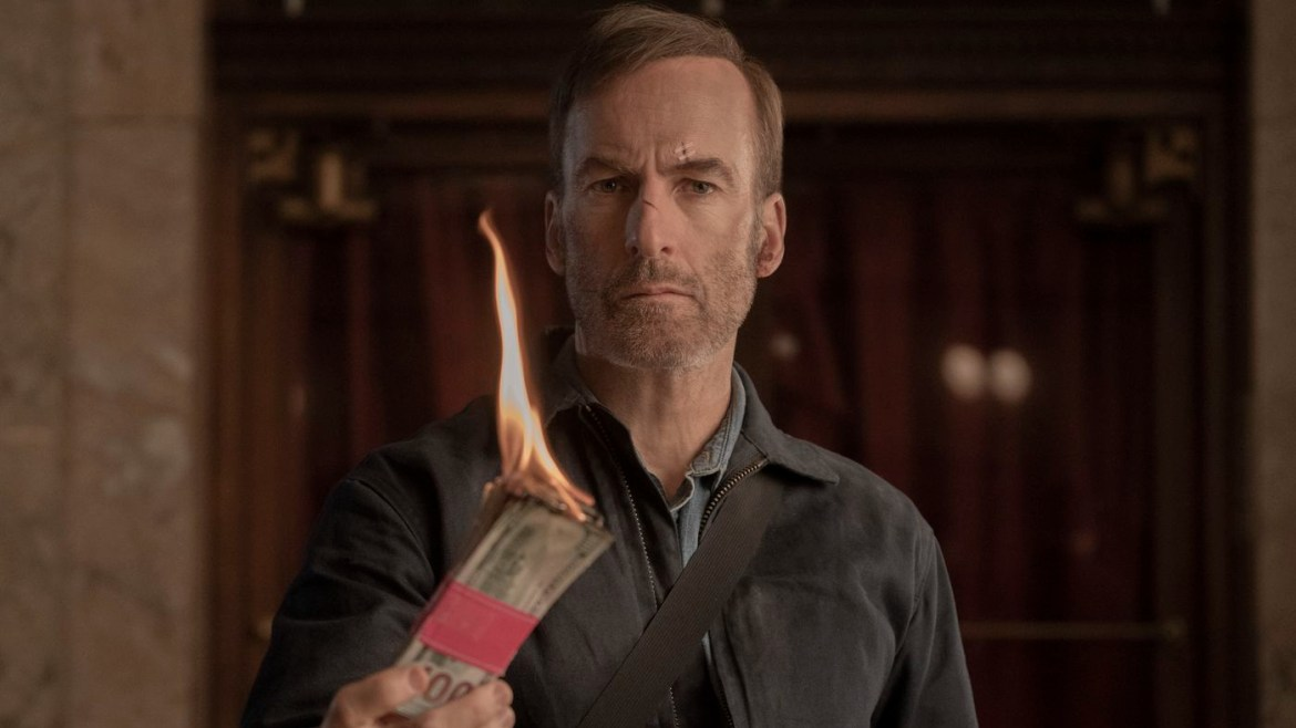 Bob Odenkirk blazing hundred dollar bills as seen in the action film Nobody, with an exclusive behind the scenes clip only seen here on DiscussingFilm.