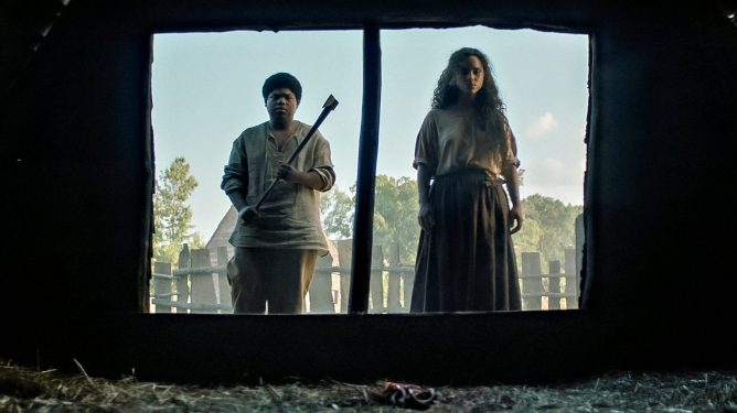 Benhamin Flores Jr. as Josh and Kiana Madeira as Sarah Fier as puritans in an old colony working on the farm as seen in FEAR STREET PART THREE: 1666 on Netflix.