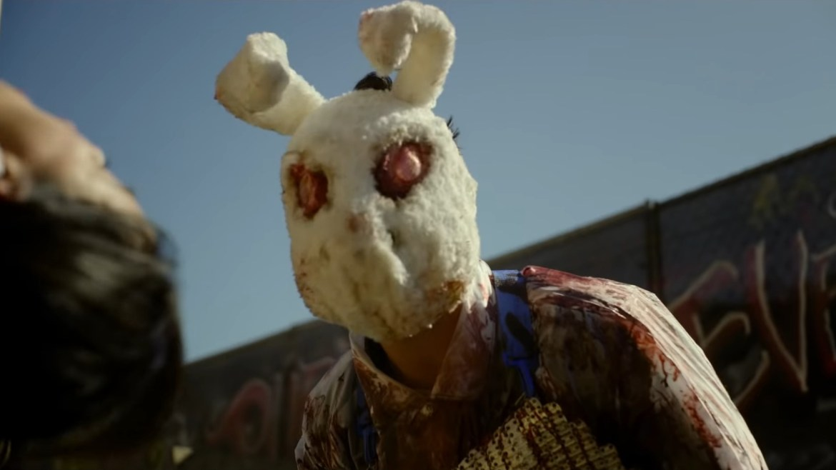 A purger wearing a bloody bunny mask looks over a helpless person in his trap as seen in the new Horror sequel THE FOREVER PURGE.