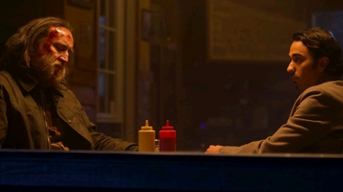 Nicolas Cage and Alex Wolff sit together in silence at an old Oregon diner as seen in the new revenge drama PIG.