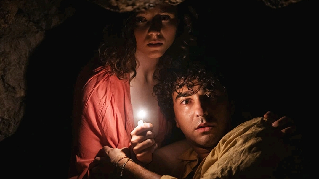 Thomasin McKenzie and Alex Wolff holding each other in fear in a dark cave by the beach as seen in the new M. Night Shyamalan horror thriller OLD.