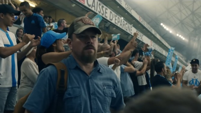 Matt Damon looking for someone in a packed French soccer/football stadium as seen in the new thriller drama STILLWATER.