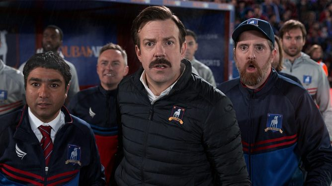 Nick Mohammed, Jason Sudeikis, and Brendan Hunt as Nate, Ted Lasso, and Coach Beard looking in shock as seen in TED LASSO season 1.