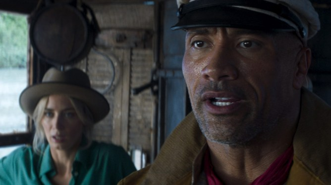 """Emily Blunt and Dwayne """"The Rock"""" Johnson going down roaring rapids in the Amazon river as seen in JUNGLE CRUISE, the latest live-action Disney movie based on an original Disneyland ride."""