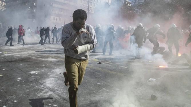 John David Washington running through tear gas in a police riot in Greece as seen in the new Netflix thriller BECKETT.