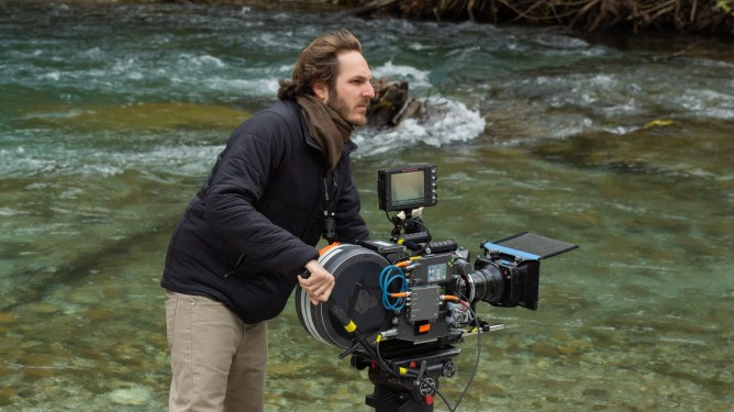 Director Ferdinando Cito Filomarino operating a camera on location in a river in Greece behind the scenes of the new Netflix thriller BECKETT.