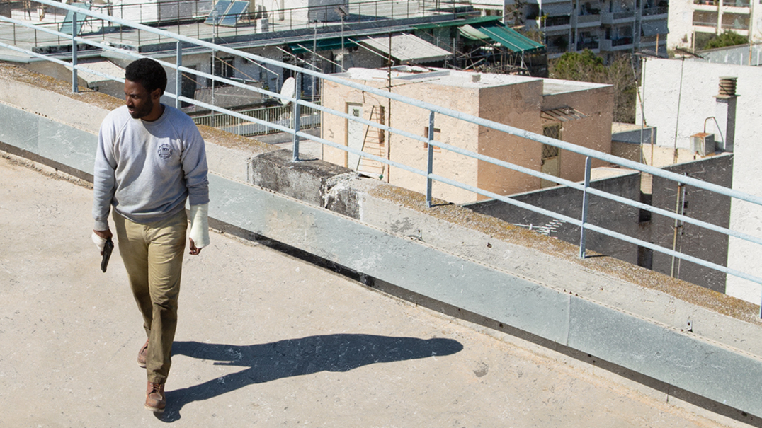 John David Washington on a Greek rooftop holding a gun as seen on the official poster for the new Netflix thriller BECKETT.