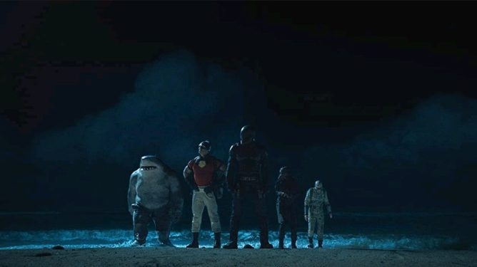 The members of Task Force X make their way onto a dark beach from the ocean waters as seen in THE SUICIDE SQUAD directed by James Gunn, taking the very top spot in our DCEU ranking from worst to best.