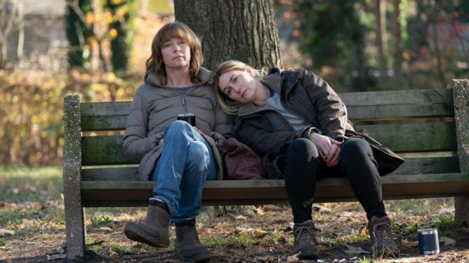 Julianne Nicholson and Kate Winslet sit together sadly on a bench as seen in the hit HBO limited series MARE OF EASTTOWN.