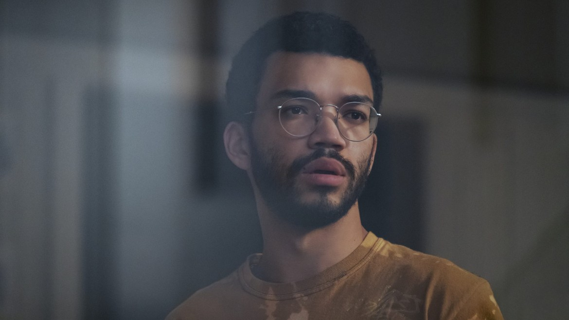 Justice Smith looking out a window and spying on his neighbors as seen in the new mystery thriller on Prime Video THE VOYEURS.