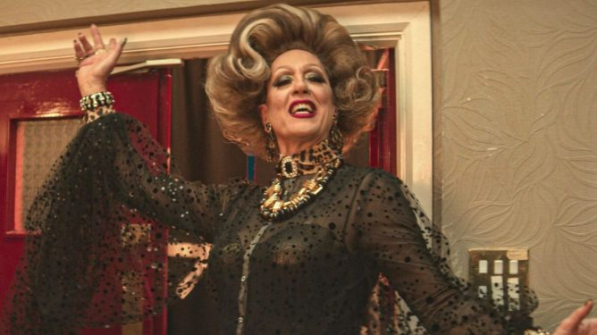 Richard E Grant posing graciously in full drag attire and makeup as Loco Chanelle in EVERYBODY'S TALKING ABOUT JAIME.