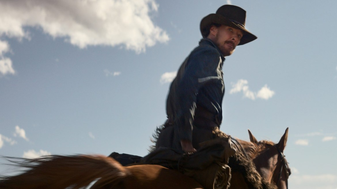 Benedict Cumberbatch wearing cowboy gear as he rides a brown horse against a blue cloudy sky as seen in THE POWER OF THE DOG, premiering at the 2021 Venice film festival and coming soon to Netflix.