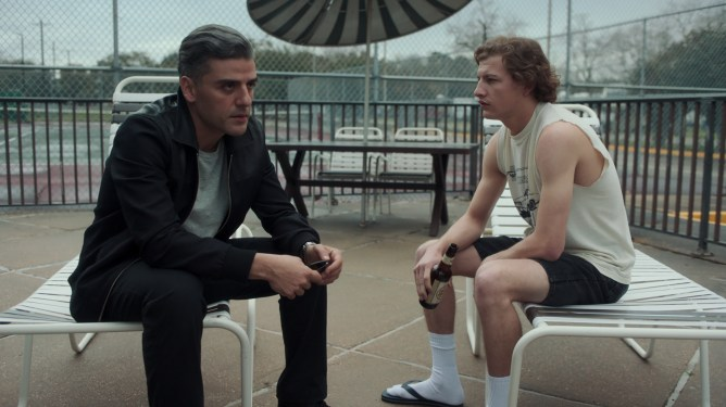 Oscar Isaac and Tye Sheridan sit together by a crummy motel pool as seen in THE CARD COUNTER directed by Paul Schrader.