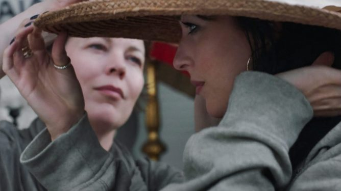 Olivia Coleman helps Dakota Johnson try on a new sun hat as seen in THE LOST DAUGHTER directed by Maggie Gyllenhaal.