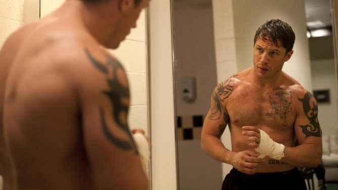 Tom Hardy looks at himself in the mirror as he prepares for an MMA fight as seen in WARRIOR directed by Gavin O'Connor, now celebrating its 10 year anniversary.