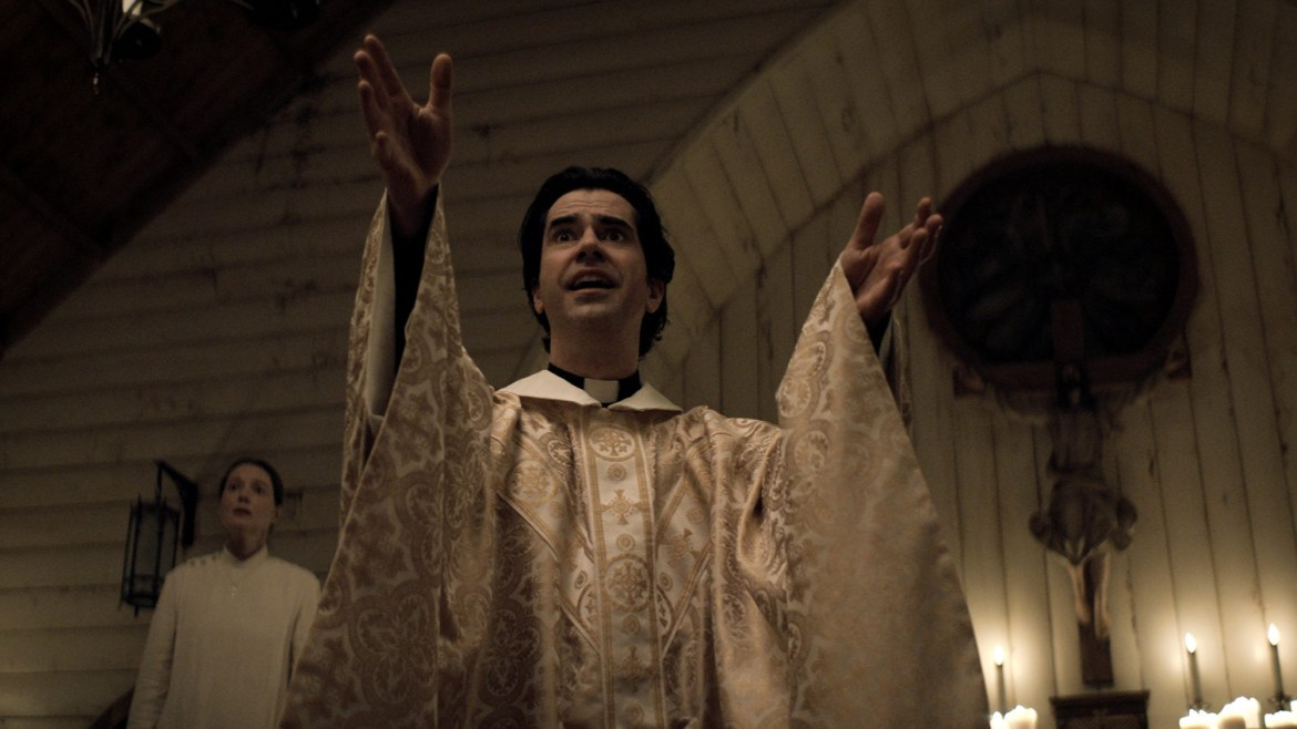 Samantha Sloyan as Bev Keane and Hamish Linklater as Father Paul lead a soulful sermon inside an old church as seen in MIDNIGHT MASS directed by Mike Flanagan on Netflix.