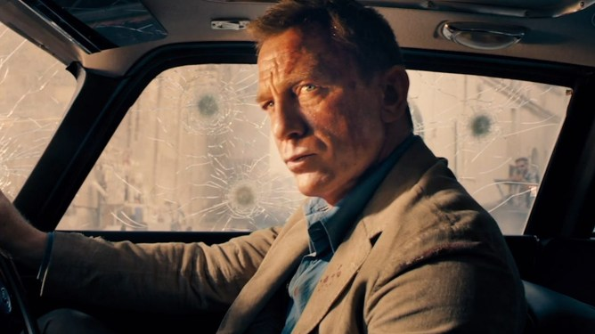 Daniel Craig as James Bond hiding from gun fire in his bullet proof silver Aston Martin car as seen in NO TIME TO DIE directed by Cary Fukunaga.