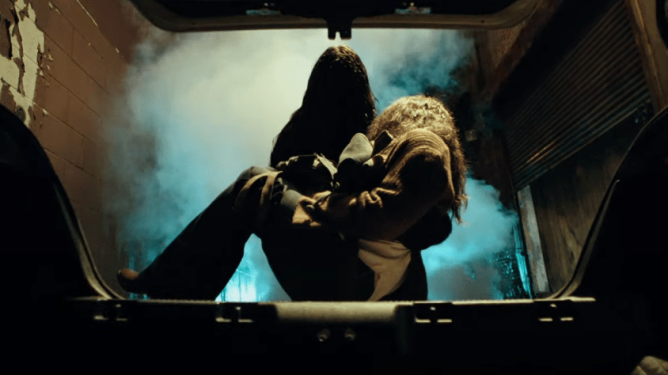 Gabriel the mysterious demonic killer dressed in black leather puts a female victim in a trunk as seen in MALIGNANT directed by James Wan.