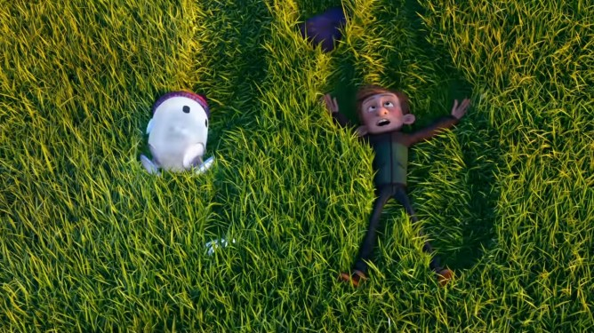 Barney, voiced by Jack Dylan Grazer, and Ron the little blue android, voiced by Zach Galifianakis, roll down a grassy hill in laughter as seen in the new animated film RON'S GONE WRONG.