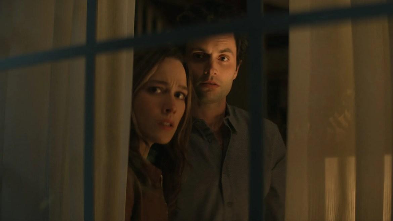 Penn Badgley as Joe Goldberg and Victoria Pedretti as Love Quinn peak through the blinds of their new suburban home in shock as seen in season 3 of the Netflix original thriller series YOU.