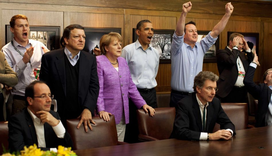 Prime Minister David Cameron of the United Kingdom, President Barack Obama, Chancellor Angela Merkel of Germany, Jose Manuel Barroso, President of the European Commission, (centre L-R) and others watch the overtime shootout of the Chelsea vs. Bayern Munich Champions League final in the Laurel Cabin conference room during the G8 Summit at Camp David, Maryland, May 19, 2012. REUTERS/White House/ Pete Souza/POOL (UNITED STATES - Tags: POLITICS SPORT SOCCER)