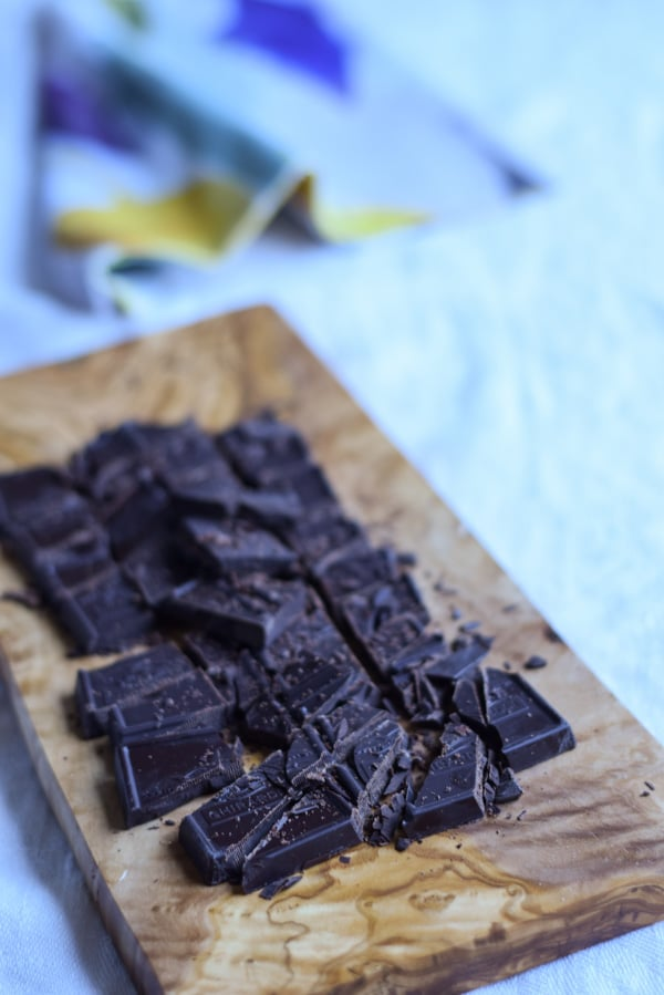 A wooden board with chopped up chocolate on it
