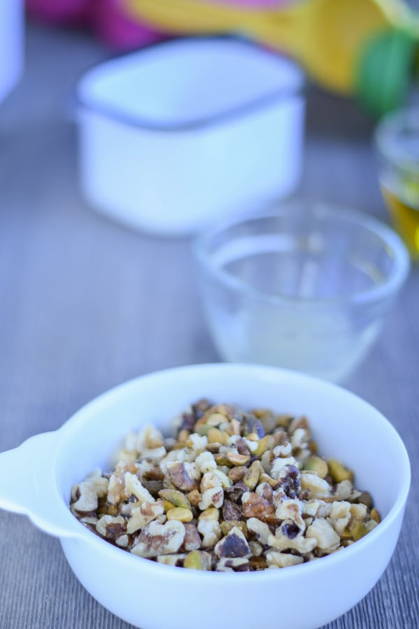 nuts in a bowl with lemon and salt behind it