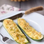 Two pieces of zucchini halves with the cheesy filling in them on a white plate
